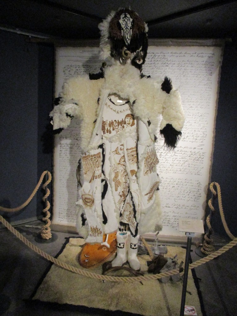 Figure 1. The sheepskin cloak, which is decorated inside with scenes from the story of Aikianpoika's life as interpreted and portrayed by Irene Kangasniemi. Above the cloak is a headdress. Below is a painted drum with a reindeer bone hammer used for playing it, a pair of boots made from white reindeer parchment, a pair of woolen socks, gloves and an axe. Behind the garment on the wall are the original court records concerning the sentencing of the noaidi. These are written in old Swedish text. Photograph and copyright Francis Joy 2018.